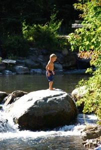 A little boy wading in the creek